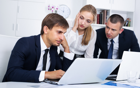 three concerned business assistants making mistake in business project in office Imagens