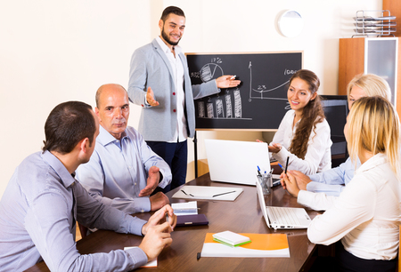 Beautiful male expert makes a presentation at a meeting in the office. Focus on the senior man Stock Photo