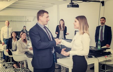 Confident businessman and young businesswoman shaking hands in office, confirming successful partnership