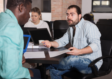 Multiracial partners developing business strategy talking at office desk in coworking space