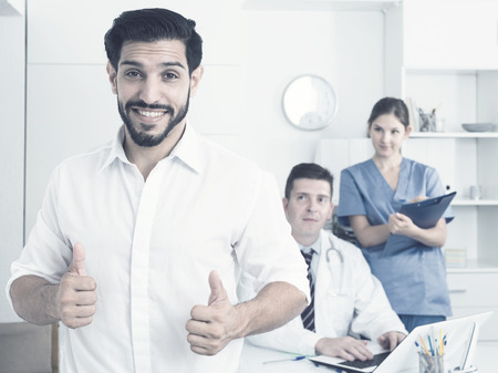 Portrait of smiling satisfied man visiting doctor giving thumbs up Фото со стока