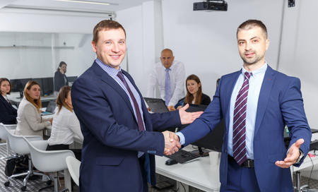 Two confident businessmen shaking hands in office confirming successful partnership