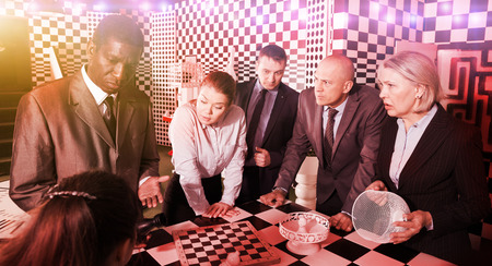 Group of adult men and women trying to get out of escape room stylized like chessboard