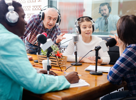 Multinational group of cheerful glad  young adults emotionally discussing in radio studio Фото со стока