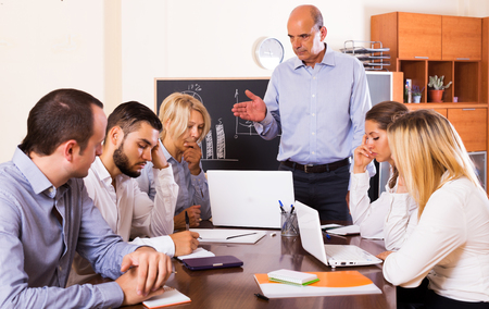 Unhappy business people during conference call indoors