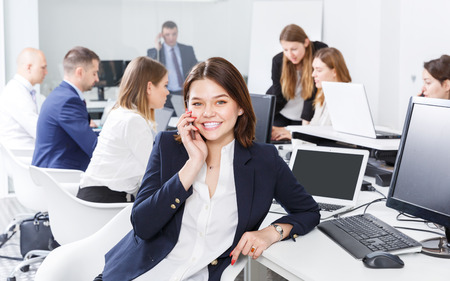 Young smiling businesswoman having phone call conversation at workplace in coworking space