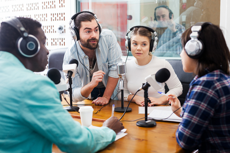 Positive male and female radio hosts interviewing guest in sound broadcasting station