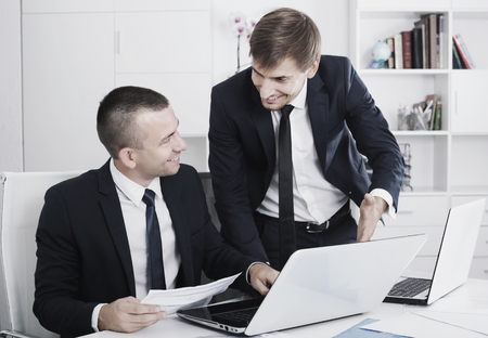 Two smiling business men colleagues working together with laptops on desk in office