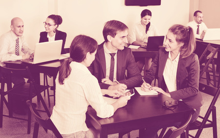 Smiling positive coworkers working effectively on business project together