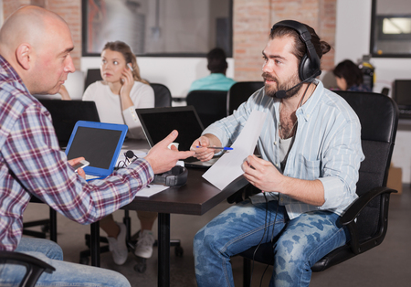 Two business partners developing strategy, talking at office desk in coworking space Stock Photo