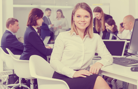 Portrait of successful business woman in coworking space with working colleagues behind