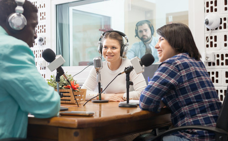 Young presenters of different nationalities in sound broadcasting station hosting live radio show