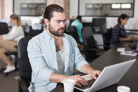 Focused bearded freelancer concentrated on work with laptop in coworking space with international team