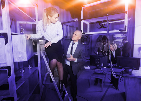 Toned image of businesspeople solving different conundrums in quest room in view as abandoned lab during corporate event.