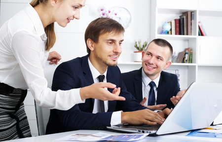 Portrait of three smiling business colleagues occupied with laptops and chatting in office Imagens