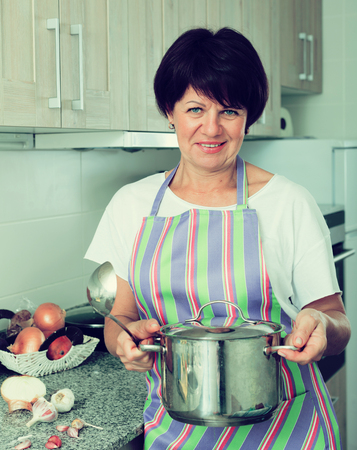 Portrait of cheerful mature woman preparing soup in cooking pot on kitchen at home