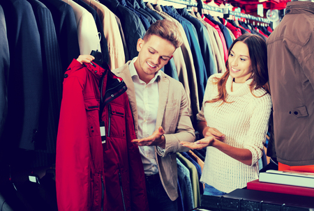 Smiling couple examining various coats in men's clothes shop
