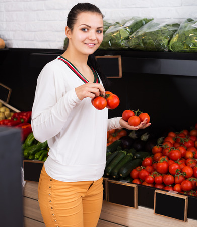 Cheerful girl deciding on tomatoes in grocery shop Stock Photo