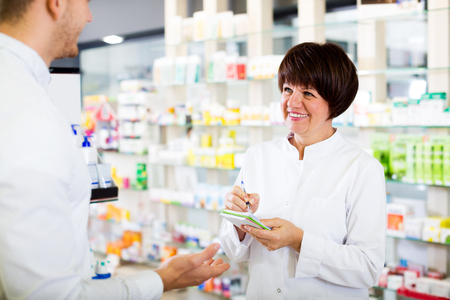 Cheerful woman druggist wearing white coat giving advice to customer in pharmacy