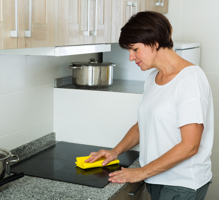 positive mature woman wiping surfaces with duster and detergent at home indoors Foto de archivo - 124767632
