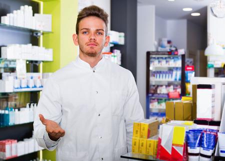 Positive glad male pharmacist wearing white coat standing among shelves in drug store