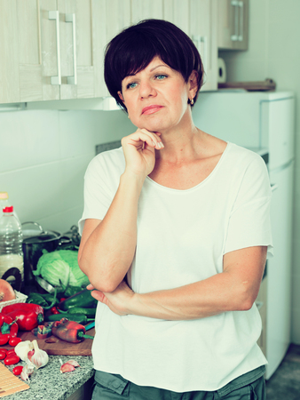 negative mature woman housewife standing with napkin at her kitchen indoors