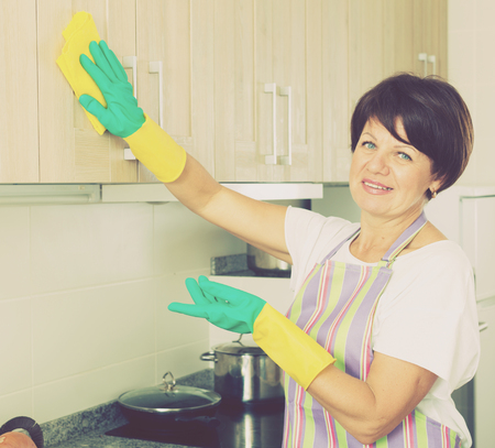 positive mature woman wiping surfaces with duster and detergent at home indoors Foto de archivo - 124767646