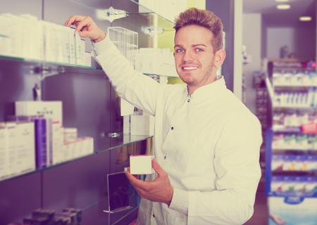 Happy adult man pharmacist wearing uniform and working in pharmaceutical shop