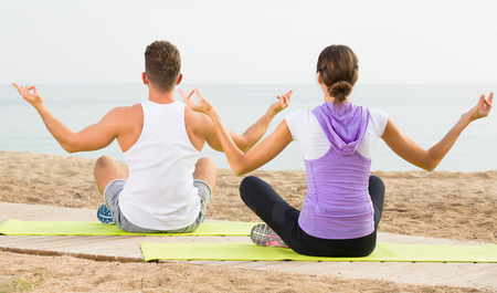 Cross-legged adult european  couple practice yoga on beach in morning Stock Photo