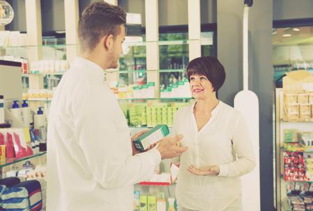 Smiling man pharmacist wearing white coat helping customers in drug store