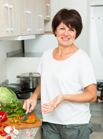glad mature woman standing at kitchen and preparing salad indoors