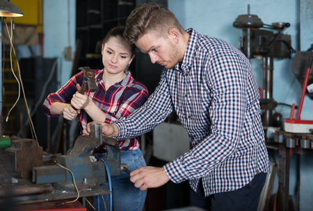 positive young masters are working together near table with instruments in workshop. Stock Photo