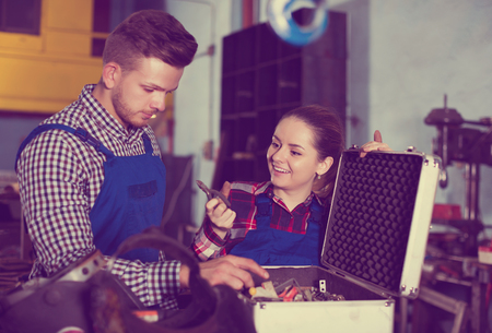 Portrait of young masters who are standing with box for tools in workshop. Stock Photo