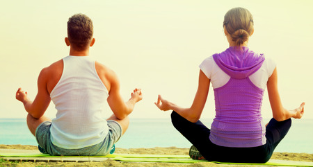 Glad woman and man sitting cross-legged do yoga poses on beach at daytime