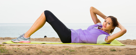 Active female training  on sea beach on sunny morning and smiling
