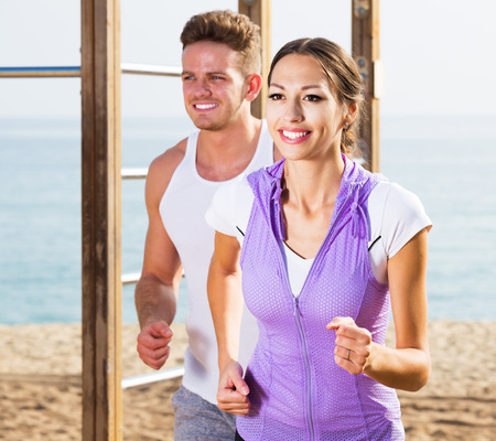 Young positive man and woman running together on beach on sunny morning
