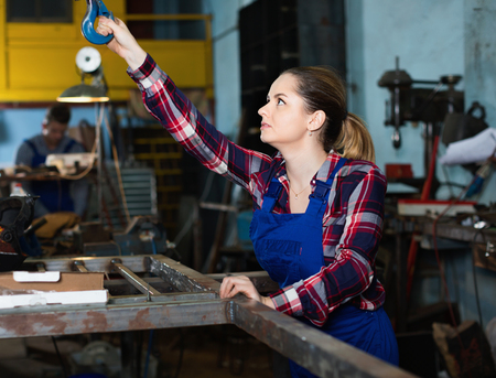 Cheerful positive  girl worker is holding lift hook equipment in workshop. Stock Photo