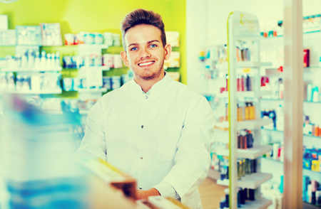 Smiling diligent  male pharmacist wearing white coat standing among shelves in drug store