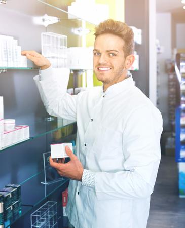 Smiling happy  male pharmacist wearing white coat standing among shelves in drug store