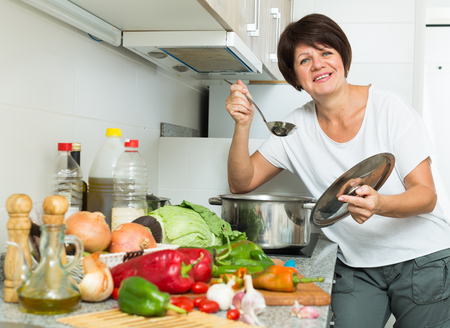 glad mature woman standing at kitchen and cooking soup in cooker indoors