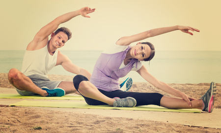 Smiling  woman and guy training on beach by sea in sunny morning Stock Photo