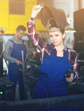 Adult female who is working in protection helmet in workshop