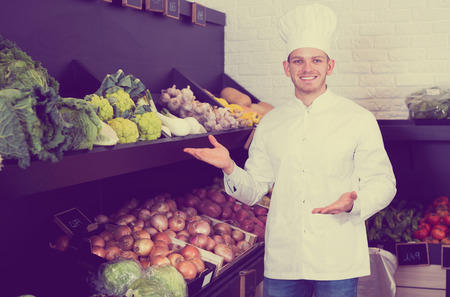 Positive young man cook deciding on best vegetables in grocery shop Stock Photo