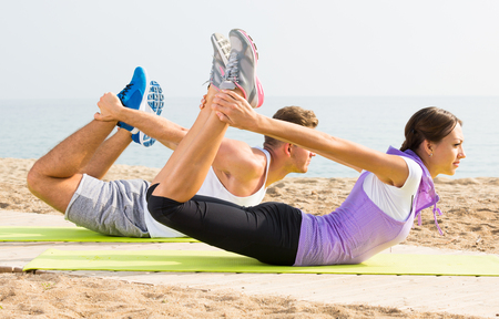 Positive guy and girl training on beach by sea in sunny morning