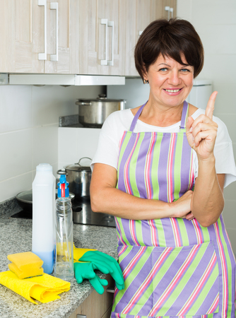 positive mature woman wiping surfaces with duster and detergent at home indoors