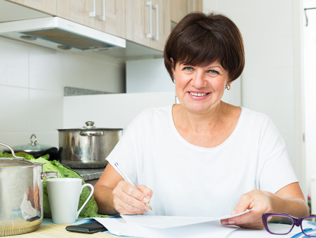 glad mature woman planning expenses and paying bills on her kitchen