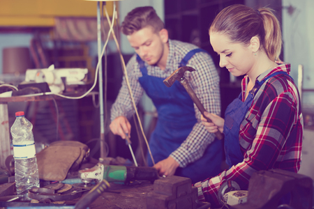 Young woman master is working with hammer in workshop