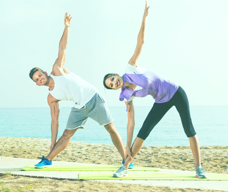 Cheerful  guy and girl practising yoga poses standing on beach by sea at daylight