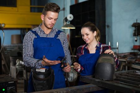Master is helping young woman to working with burning in workshop. Stock Photo