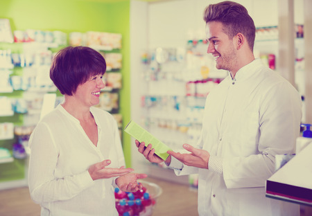 Smiling man druggist in white coat giving advice to customers in pharmacy